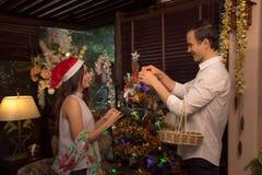 El par joven adorna el árbol de navidad en una casa/un concepto imerry de la Navidad Fotografía de archivo libre de regalías