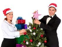 El par joven adorna el árbol de navidad Fotos de archivo libres de regalías