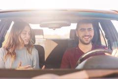 El par joven alegre tiene viaje auto, la familia tiene conversación agradable mientras que viaja en coche, el varón joven y femen foto de archivo