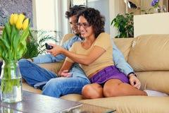 El par joven atractivo se sienta en un sofá con un ordenador portátil en una tabla en una sala de estar Foto de archivo libre de regalías