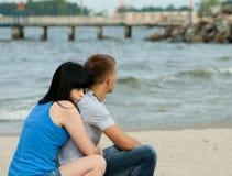 El par joven cariñoso se está sentando cerca del mar Fotografía de archivo