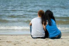 El par joven cariñoso se está sentando cerca del mar Foto de archivo
