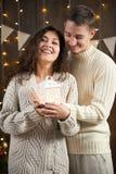 El par joven celebra el Año Nuevo Luces y decoración de la Navidad Vestido en el suéter blanco Árbol de abeto en backgroun de mad Fotos de archivo libres de regalías