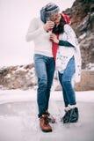 El par joven con las tazas de té caliente en sus manos es kisssing y permanente en charco del agua derretida Fotografía de archivo