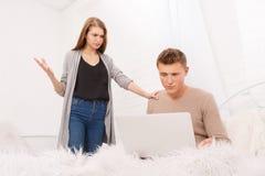 El par joven de la familia en el dormitorio, la muchacha demanda al individuo que utiliza el ordenador portátil imagenes de archivo