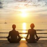 El par joven de la yoga está meditando en la posición de Lotus respecto a la playa del mar Fotografía de archivo libre de regalías