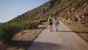 El par joven del inconformista camina en el camino de la montaña en puesta del sol metrajes
