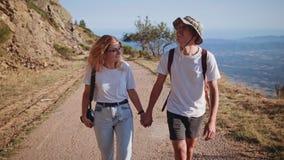 El par joven del inconformista camina en el camino de la montaña en puesta del sol almacen de metraje de vídeo