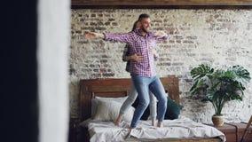 El par joven divertido está bailando en la cama que se divierte en dormitorio y la risa del estilo del desván Gente feliz, forma  metrajes