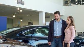 El par joven elige el coche en la representación metrajes