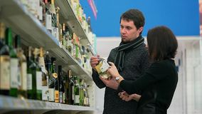 El par joven elige el vino en un colmado para ir a visitar a amigos metrajes