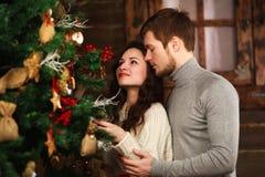 El par joven en amor adorna el árbol de navidad en casa Fotografía de archivo