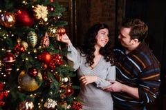 El par joven en amor adorna un árbol de navidad en casa Imagen de archivo
