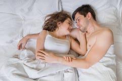 El par joven en amor está mintiendo en cama y el abrazo Están mirando en sus ojos imagen de archivo libre de regalías