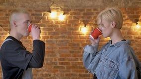 El par joven en amor está tintineando los vidrios, contacto visual, concepto del amor, fondo del ladrillo metrajes