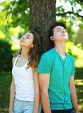 El par joven en el goce de los auriculares escucha la música en parque de la ciudad cerca de árbol del tronco Imágenes de archivo libres de regalías