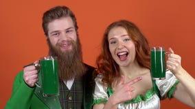 El par joven en los trajes que celebran día del ` s de St Patrick aislado en la pared anaranjada anima la cerveza verde metrajes