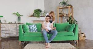 El par joven en sala de estar en el sofá verde, hombre quiere ver TV, mujer lo abraza metrajes