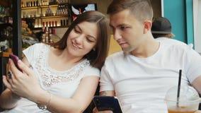 El par joven en un café, muchacha muestra a hombre una foto o una nueva aplicación en un teléfono móvil metrajes