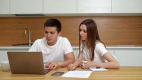 El par joven es ordenador portátil del uso que se sienta en el abarcamiento de la cocina metrajes