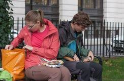 El par joven está comiendo la comida en un banco en el parque en Londres Fotografía de archivo