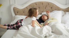El par joven está durmiendo junto abrazando en la cama en casa La niña activa la está despertando los padres durmientes metrajes
