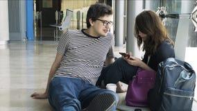 El par joven está esperando su vuelo en el aeropuerto de Valencia almacen de video