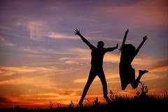 El par joven está llevando a cabo las manos en una silueta de la puesta del sol del fondo Fotografía de archivo libre de regalías