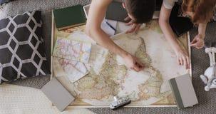 El par joven está planeando la ruta que viaja que señala los lugares para la visita en un mapa usando los pernos de la bandera ro metrajes