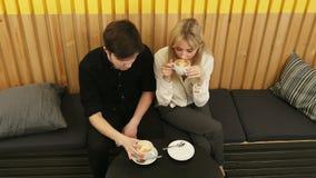 El par joven est? bebiendo el caf? y est? hablando mientras que se sienta en el caf? metrajes