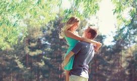 El par joven feliz en el abrazo del amor disfruta de día de primavera, hombre cariñoso que se sostiene encendido da a su mujer ju Fotografía de archivo libre de regalías