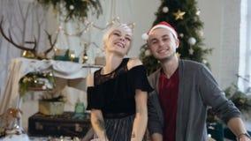 El par joven feliz está celebrando la tostada de consumición del Año Nuevo o de la Navidad, tintineando los vidrios en casa en el metrajes