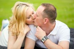 El par joven, feliz miente en una hierba y un beso Imagen de archivo libre de regalías