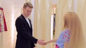 El par joven feliz que se divierte elige la ropa en el cuarto apropiado metrajes