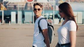 El par joven feliz va con equipaje cerca del aeropuerto o del ferrocarril El concepto de viaje, vacaciones, días de fiesta almacen de video