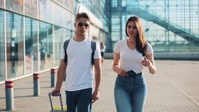 El par joven feliz va con equipaje cerca del aeropuerto o del ferrocarril El concepto de viaje, vacaciones, días de fiesta metrajes