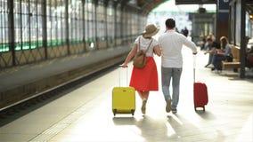 El par joven feliz va con equipaje cerca del aeropuerto o del ferrocarril El concepto de viaje, vacaciones, d?as de fiesta almacen de video