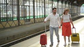 El par joven feliz va con equipaje cerca del aeropuerto o del ferrocarril El concepto de viaje, vacaciones, d?as de fiesta metrajes