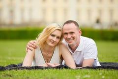 El par joven, feliz y sonriente miente en una hierba Imágenes de archivo libres de regalías