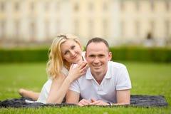 El par joven, feliz y sonriente miente en una hierba Imagen de archivo libre de regalías
