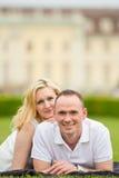El par joven, feliz y sonriente miente en una hierba Imagen de archivo