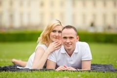 El par joven, feliz y sonriente miente en una hierba Fotos de archivo libres de regalías