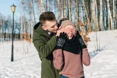 El par joven hermoso en amor camina el parque en un día de invierno soleado claro foto de archivo