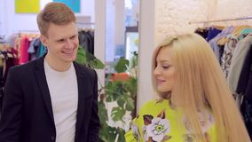 El par joven hermoso en la tienda de ropa del ` s de las mujeres elige un vestido para ella almacen de metraje de vídeo