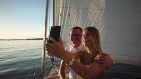 El par joven hermoso está tomando el selfie a bordo de un yate almacen de metraje de vídeo