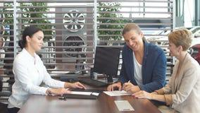 El par joven hermoso firma documentos en la sala de exposici?n de la representaci?n almacen de metraje de vídeo