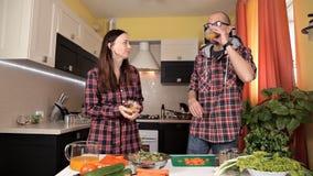El par joven hermoso se está alimentando y está sonriendo mientras que cocina en cocina en casa almacen de metraje de vídeo