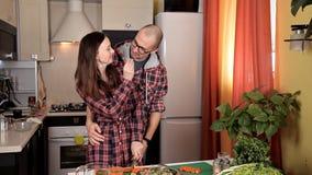 El par joven hermoso se está alimentando y está sonriendo mientras que cocina en cocina en casa almacen de video