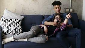 El par joven lindo en el sofá, muchacha caucásica atractiva que miente en su ` hermoso s del novio del mulato traslapa Él está in almacen de metraje de vídeo