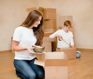 El par joven pone cosas en las cajas de cartón para trasladarse a una nueva casa Imagen de archivo